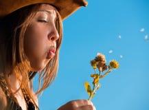 Girl blowing dandelions blue sky. Young teenage girl blowing dandelions Stock Images
