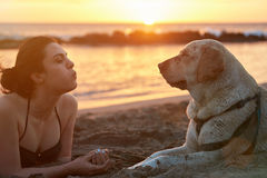 Girl blowing in dog nose Royalty Free Stock Images