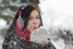 Girl blowing fluffy snowflakes Stock Photos