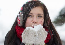 Girl blowing fluffy snowflakes Royalty Free Stock Images