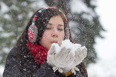 Girl blowing fluffy snowflakes Royalty Free Stock Image