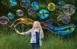 Girl blowing giant rainbow color soap bubbles