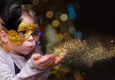 Girl blowing golden dust stock images