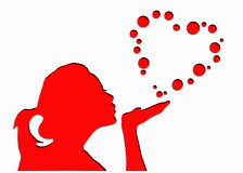 Girl blowing heart shape bubbles Royalty Free Stock Images