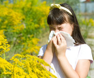 Girl is blowing her nose. Allergic to bloom flowers Royalty Free Stock Image