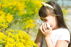Girl is blowing her nose. Allergic to bloom flowers Stock Photos