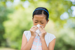 Girl blowing her nose with handkerchief while sneezing Royalty Free Stock Photo