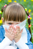 Girl is blowing her nose. Little girl is blowing her nose while sitting on green meadow Stock Photos