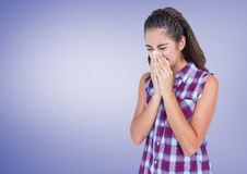 Girl blowing her nose in tissue with purple background Royalty Free Stock Photo