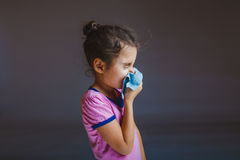 Girl blowing his nose into handkerchief on a gray Royalty Free Stock Photography