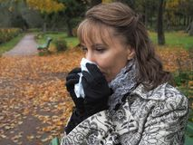 Girl blowing his nose into a paper handkerchief in autumn park. Girl blowing his nose into a paper handkerchief Royalty Free Stock Photos