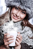 Girl blowing on hot drink Royalty Free Stock Images