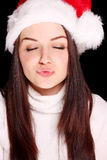 Girl blowing kiss in christmas hat Royalty Free Stock Image