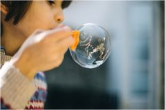 Girl Blowing a Large Bubble Royalty Free Stock Images
