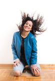 Girl with blowing long curly hair. Beautiful young girl on knees swinging head and enjoying movement of her blowing long curls Stock Images