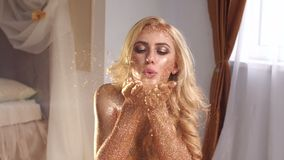 Girl blowing millions of pieces of golden glitter. Beautiful girl with golden skin and makeup blowing on golden dust from hands on camera. Girl blowing millions stock footage