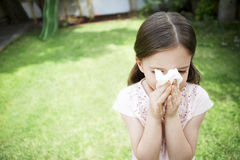 Girl Blowing Nose In Backyard. Young girl blowing nose with tissue paper in backyard Royalty Free Stock Photo