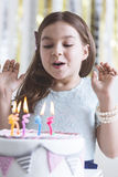 Girl blowing out birthday candles Royalty Free Stock Images