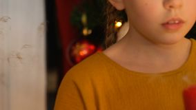 Girl blowing out candle, making wish on Christmas, faith in miracle, closeup. Stock footage stock footage