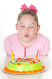 Girl blowing out candles Stock Photos