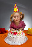 Girl blowing out candles Royalty Free Stock Photography