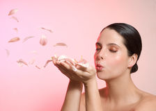 Girl blowing petal. Beauty shot of a young woman in pink background blowing petals Stock Image
