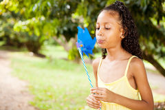 Girl blowing on a pinwheel Stock Photography