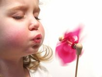 Girl blowing pinwheel Royalty Free Stock Photography
