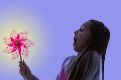 Girl blowing a pinwheel with a blue background Royalty Free Stock Photography