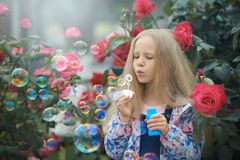 Girl blowing rainbow color soap bubbles in the bush of roses