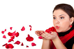 Girl blowing red petals Stock Photography