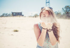 Girl blowing sand Stock Photography