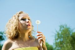 Girl blowing seeds of dandelion Royalty Free Stock Photography