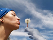 Girl blowing seeds out of a dandelion Royalty Free Stock Images