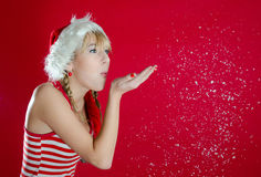 Girl blowing snow. Portrait of beautiful sexy girl wearing santa claus clothes on red background Stock Image