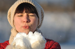 Girl blowing snow. Photo of young woman blowing snow from her hands Stock Photography