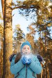 Girl blowing on the snow. In the forest Stock Photography