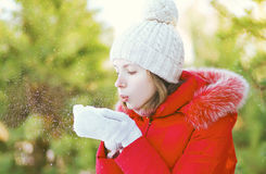 Girl blowing on snow in hands, winter Stock Photo