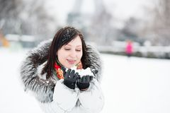 Girl blowing on snow in her hands Stock Photo