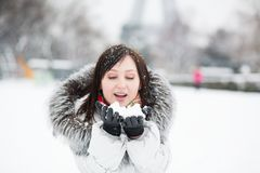 Girl blowing on snow in her hands Royalty Free Stock Photos