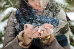 Girl blowing on snow in her hands in winter.Glamorous colorful manicure stock images