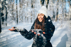 Girl Blowing Snow outdors in the forest catch snowflakes and smile. Girl Wearing Warm Winter Clothes And Hat Blowing Snow outdors in the forest catch snowflakes Stock Images