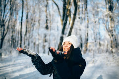 Girl  Blowing Snow outdors in the forest catch snowflakes. Girl Wearing Warm Winter Clothes And Hat Blowing Snow outdors in the forest catch snowflakes Stock Photography