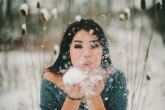 Girl Blowing Snow Toward Camera Stock Photo