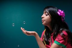 Girl blowing soap bubble Stock Image