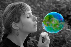 Girl blowing a soap bubble in the shape of a planet. Planet Earth. Earth. Conceptual image. Ecological concept stock photography