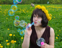 Girl blowing soap bubbles Stock Images