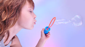 Girl  blowing soap bubbles against bright background Stock Photo