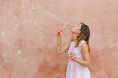 Girl blowing soap bubbles against colourful backdrop Royalty Free Stock Images