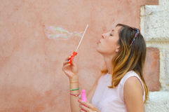 Girl blowing soap bubbles against colourful backdrop Stock Photography